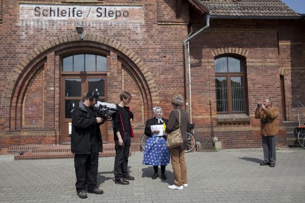 Vor dem Spaziergangs gegen Abbaggerung unterhält sich Edith Penk vor dem Bahnhof von Schleife mit einem Kamerateam und Menschen aus Rohne