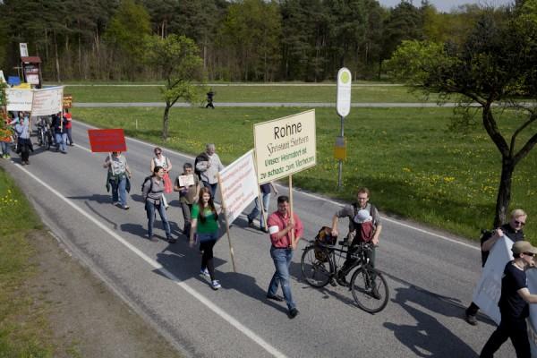 """Ingo Schuster trägt das """"Ortsschild"""" seines Heimatdorfs Rohne bei dem Spaziergang gegen Abbaggerung"""